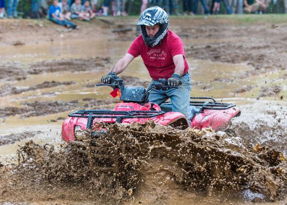 man driving an ATV through the mud