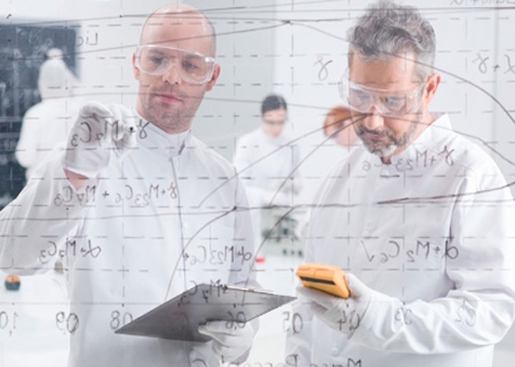 scientists writing on see through board
