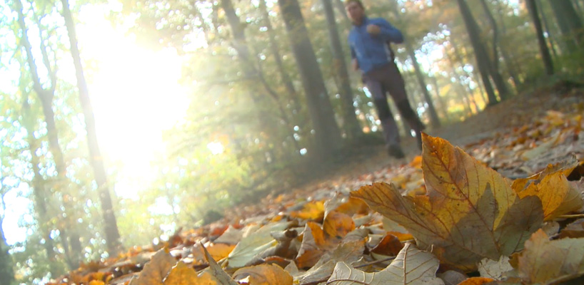 man running through fall foilage