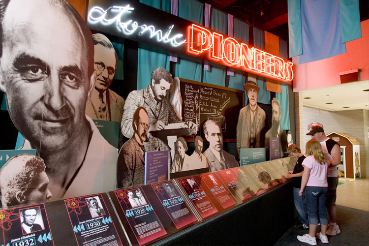 a family of three looking at the atomic pioneers exhibit at the museum in oak ridge tn