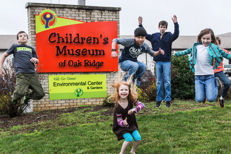 kids jumping in front of the children museum sign in oak ridge