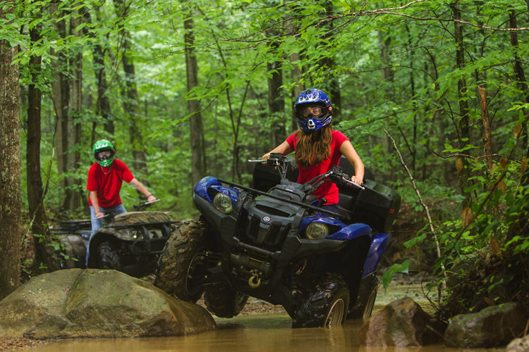 woman and man driving ATVs through water in windrock park