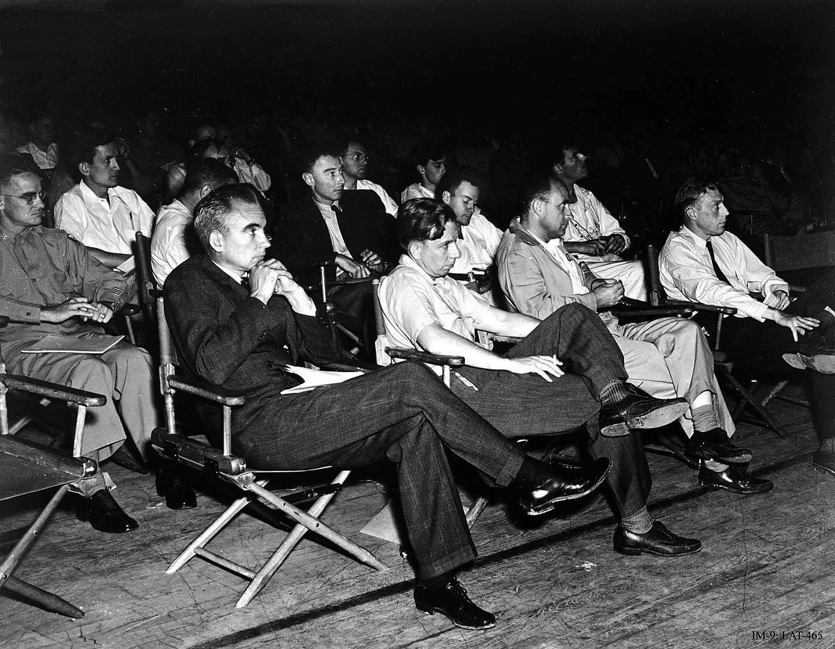 black and white photo of men sitting in chairs watching a scene
