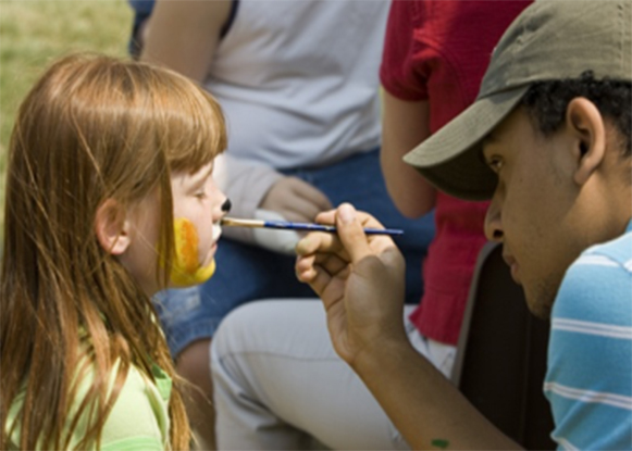 girl having her face painted at secret city festival