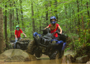 girl taking an atv through the water at windrock park