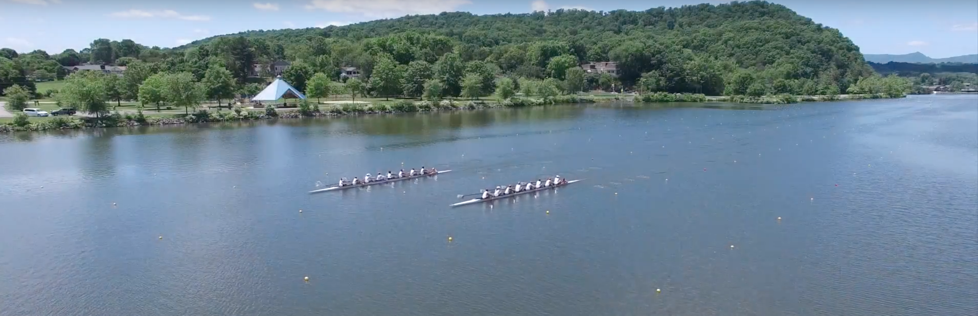 two rowing teams on the water in the distance