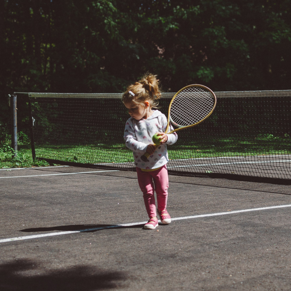 little girl with tennis ball and racket