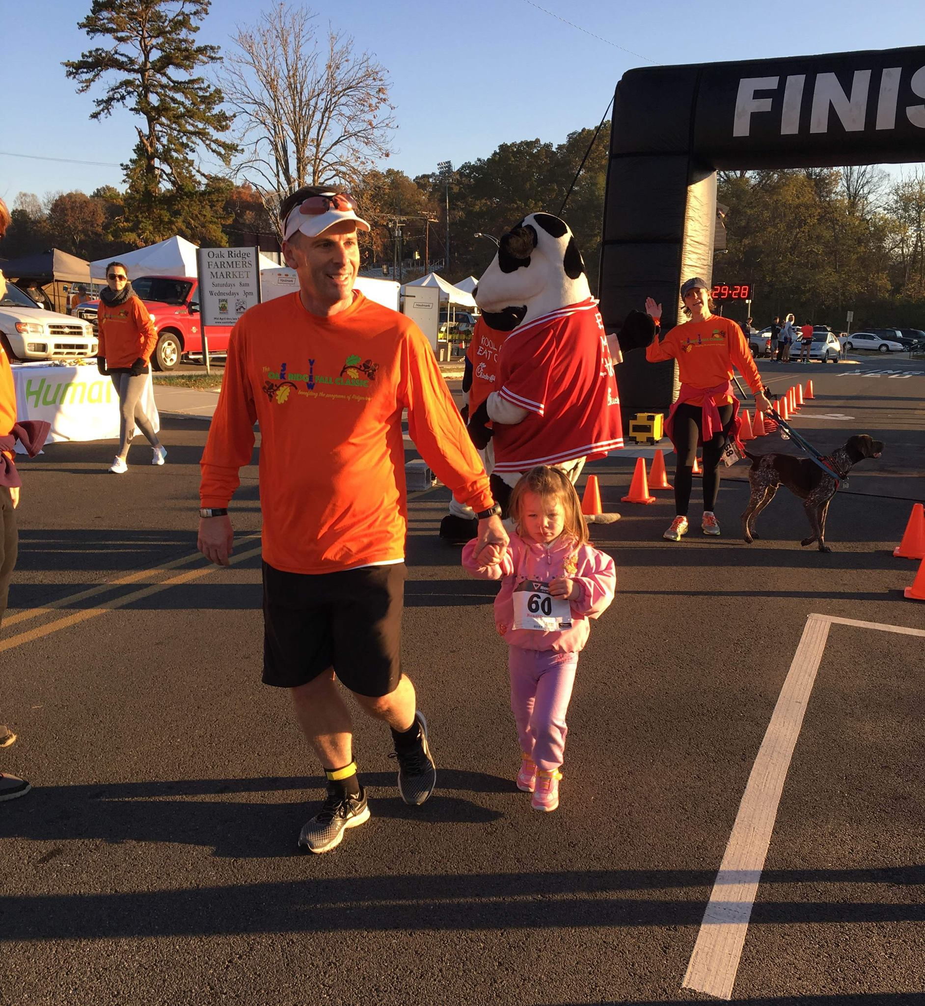 dad and his little girl holding hands after finishing a race