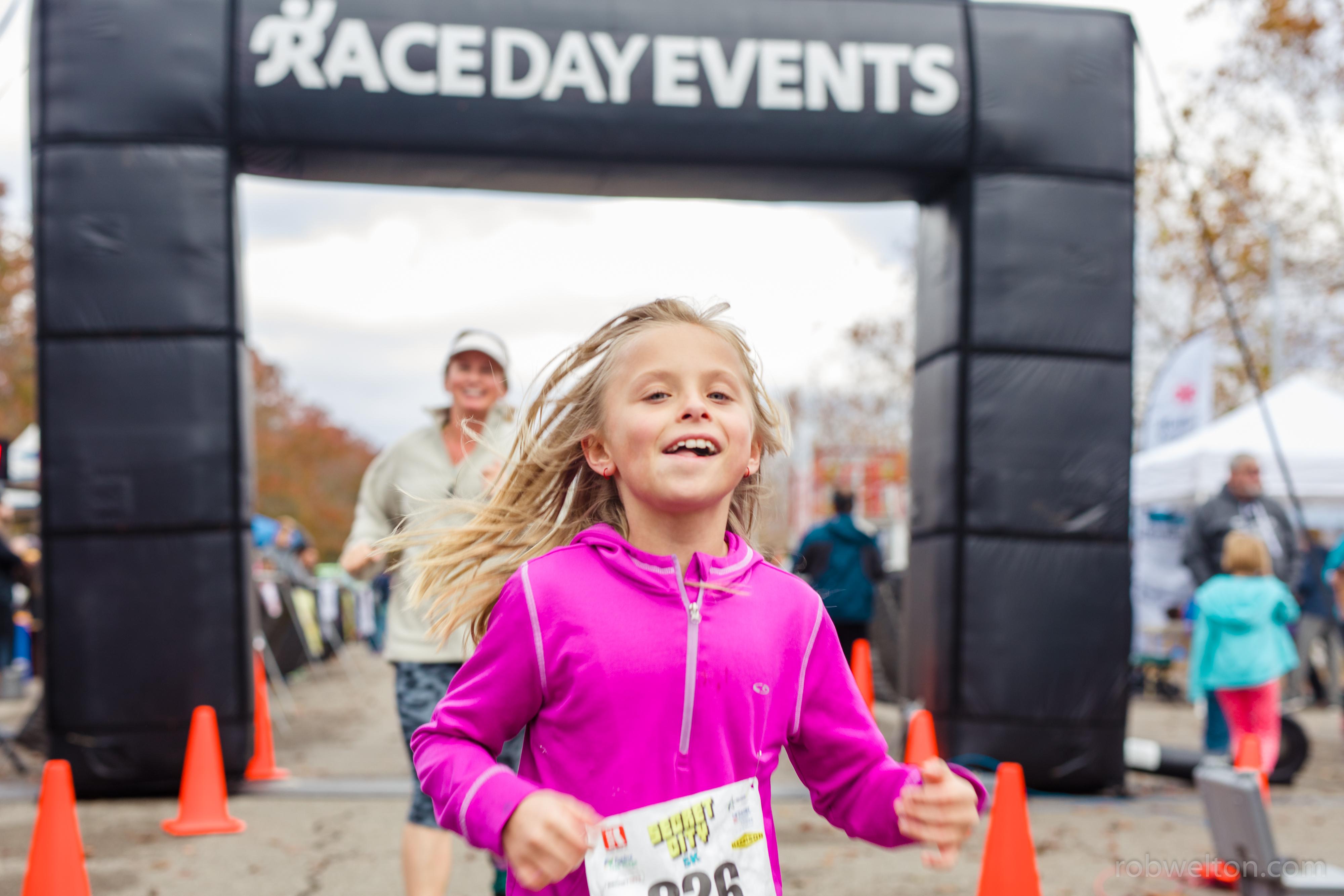 little girl running across the finish line of big race