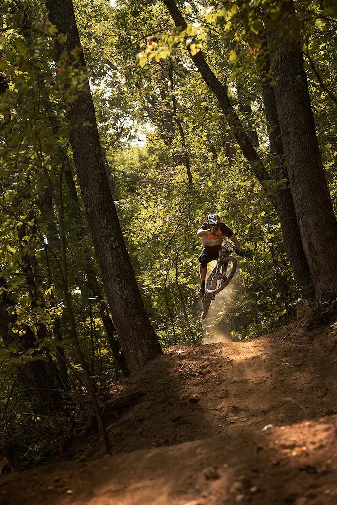 bicyclist catching some air on biking trail in haw ridge park