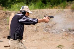 A man firing a gun at an outdoor shooting range.